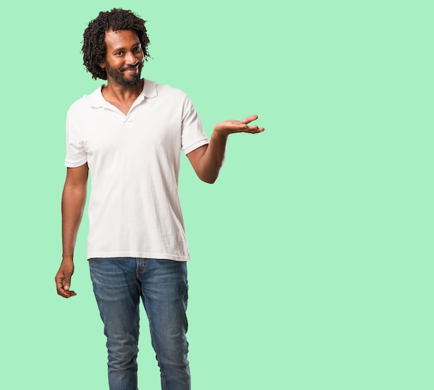 Africano-americano bonito segurando algo com as mãos, mostrando um produto, sorrindo e alegre, oferecendo um objeto imaginário