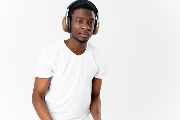 Africano-americano com fones de ouvido, ouvindo música, estilo de vida, tecnologia, luz de fundo