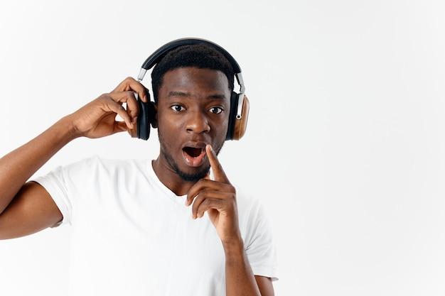 Africano-americano em fones de ouvido, ouvindo música estilo de vida de fundo claro. foto de alta qualidade