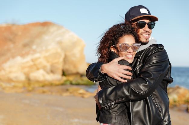 Africano casal apaixonado caminhando ao ar livre na praia.