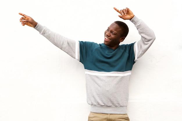 Africano jovem bonito apontando para fora no fundo branco