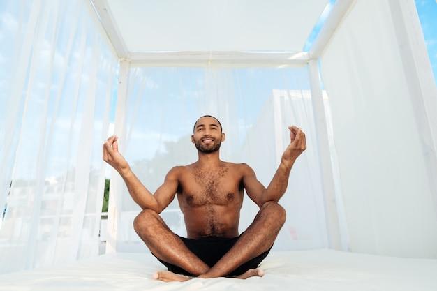 Africano jovem bonito em shorts sentado e meditando na cama da praia