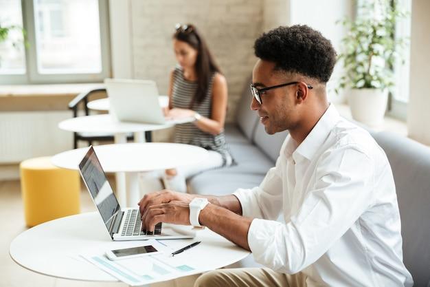 Africano jovem concentrado sentado coworking