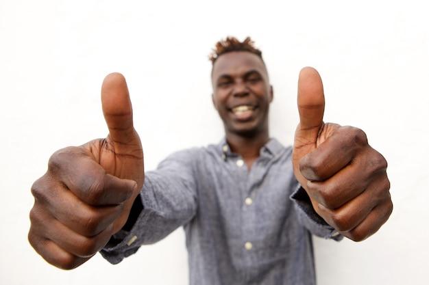 Africano jovem positivo sorrindo com dois polegares para cima
