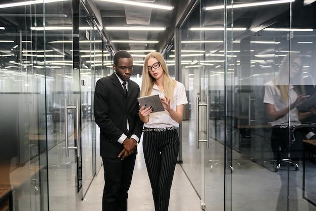 Africano masculino e trabalhadores de escritório feminino caucasiano com tablet pc em pé no corredor do escritório vazio e discutir o novo projeto.
