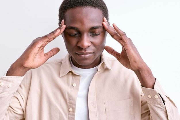 Africano negro tocando templos, tendo pensamentos profundos com os olhos fechados, concentrados na mente. parede branca isolada do estúdio