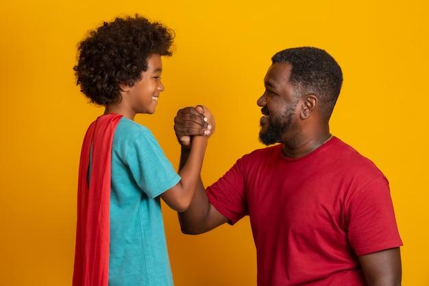 Africano pai e filho jogando super-herói na hora do dia. pessoas se divertindo parede amarela. conceito de família amigável.
