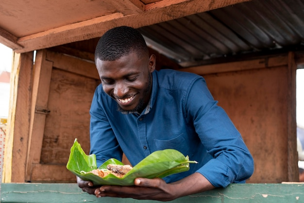 Africano pegando comida de rua
