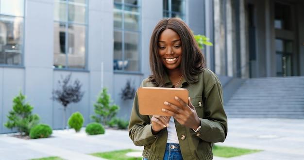 Afro-americana alegre elegante jovem tocando ou rolando no dispositivo tablet e parado na rua da cidade. linda mulher feliz usando computador gadget e sorrindo. lado de fora. assistindo video.