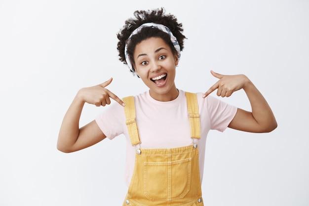 Afro-americana bonita, charmosa, ativa e otimista, de macacão amarelo e bandana apontando para si mesma, inclinando a cabeça e sorrindo amplamente, orgulhosa de seus feitos sobre a parede cinza