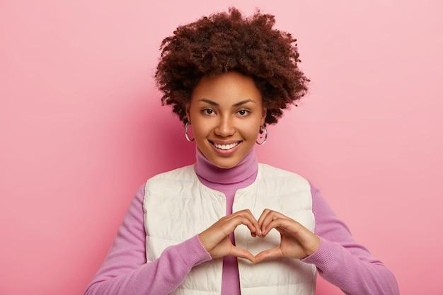 Afro-americana carinhosa mostra gestos de coração, expressa amor, admiração e simpatia, sorri feliz, mostra dentes brancos, demonstra afeto, usa colete branco.