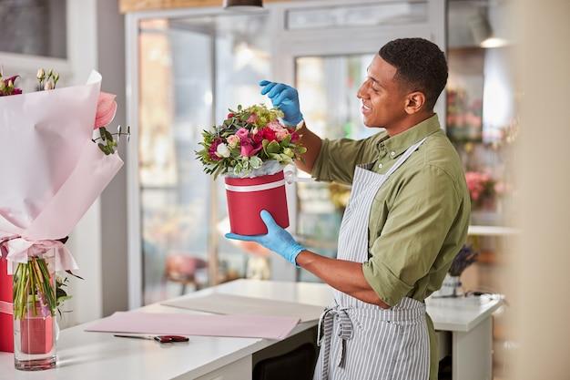 Afro-americana entusiasta da floricultura, sentada à mesa branca, arrancando flores desnecessárias de um arranjo floral