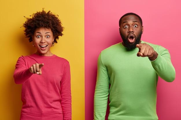 Afro-americana jovem e animada indicam em frente, apontam com expressões de surpresa, usam roupas vistosas, sentem-se envergonhados, posam sobre duas paredes coloridas. nossa olha ai