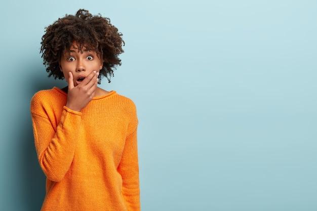 Afro-americana jovem e emocional com medo tem olhos arregalados, cobre a boca, tenta ser muda