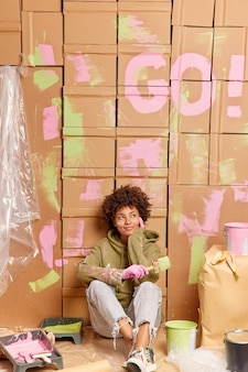 Afro-americana jovem e pensativa, sentada no chão, faz uma pausa após reformar uma nova casa, pega pincel para pintar paredes, pensa em novas mudanças no interior de um novo apartamento, descansa após a reforma