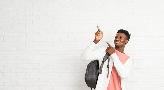 Afro-americana jovem estudante apontando com o dedo indicador uma ótima idéia e olhando para cima