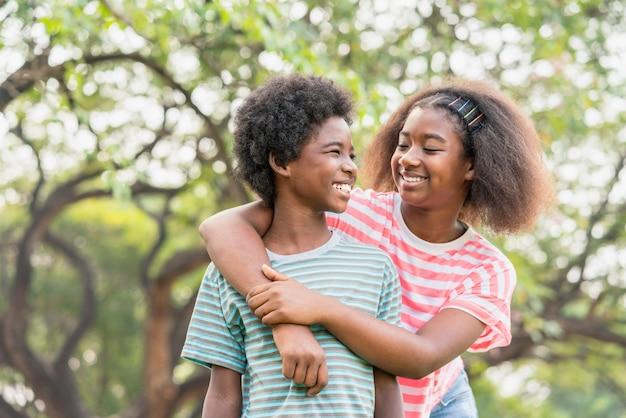 Afro-americana jovem irmã e irmão sorrindo se olham no parque