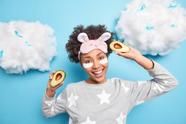 Afro-americana jovem positiva com cabelo encaracolado segura metades de abacate, dança despreocupada de pijama e aplica protetores de beleza sob os olhos estando de bom humor