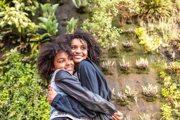 Afro americana mãe e filha abraçando uns aos outros.