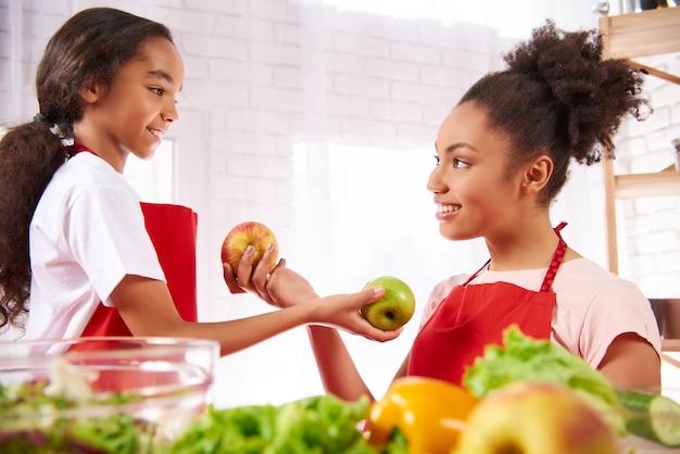 Afro-americana mãe e filha em aventais comem