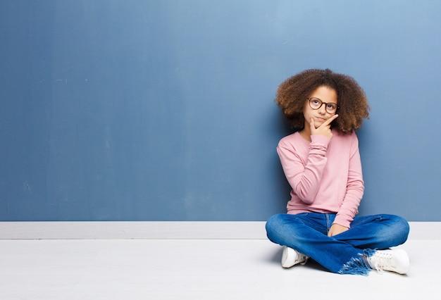 Afro-americana menina olhando sério, pensativo e desconfiado, com um braço cruzado e mão no queixo, ponderando opções sentado no chão