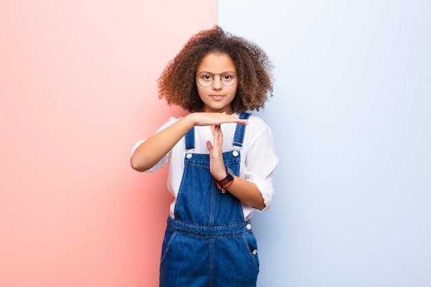 Afro-americana menina olhando sério, popa, com raiva e descontente, fazendo sinal de tempo contra a parede plana