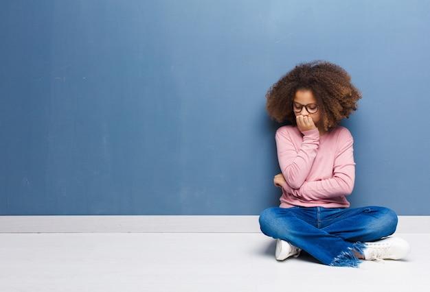 Afro-americana menina se sentindo sério, pensativo e preocupado, olhando de soslaio com a mão pressionada sobre o queixo, sentado no chão