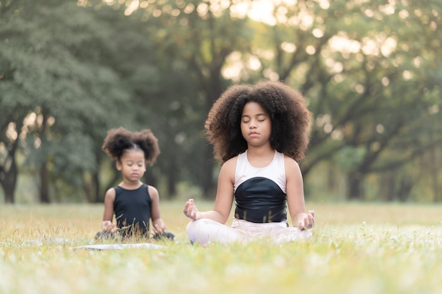 Afro-americana menina sentada no tapete praticando meditar ioga no parque ao ar livre