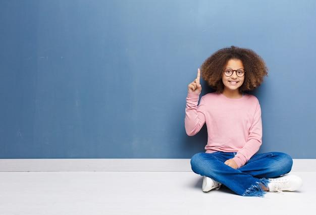 Afro-americana menina sorrindo alegremente e alegremente, apontando para cima com uma mão para copiar espaço sentado no chão