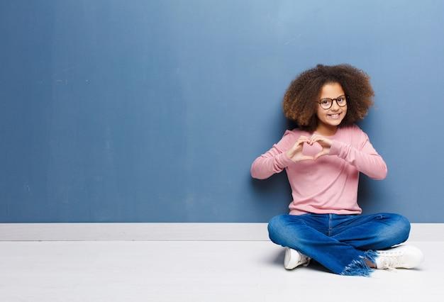 Afro-americana menina sorrindo e se sentindo feliz, fofo, romântico e apaixonado, fazendo formato de coração com as duas mãos, sentada no chão