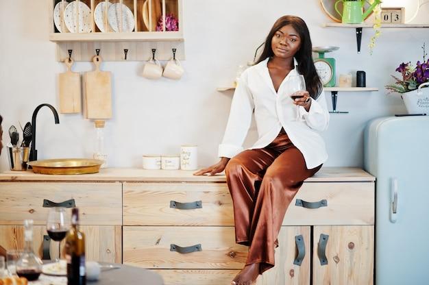 Afro-americana mulher bebendo vinho na cozinha no seu encontro romântico.