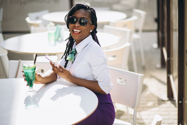 Afro americana mulher com telefone bebendo em um café