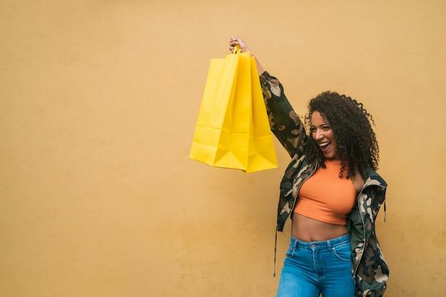 Afro-americana mulher latina segurando sacolas de compras.