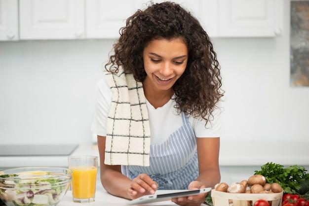 Afro-americana mulher olhando para tablet na cozinha