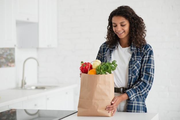 Afro-americana mulher segurando legumes saco
