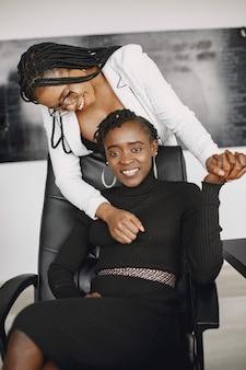 Afro-americanas alegres empresárias em ternos elegantes na mesa