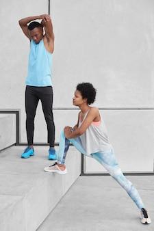 Afro-americano adulto masculino levanta as mãos, aquece antes do treinamento cardiovascular. mulher de pele escura em leggings e tênis estica as pernas, se prepara para correr a maratona. duas pessoas esportivas na escada