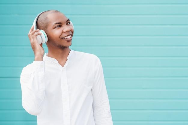 Afro-americano alegre com uma camisa branca e fones de ouvido posando para a câmera em uma parede azul