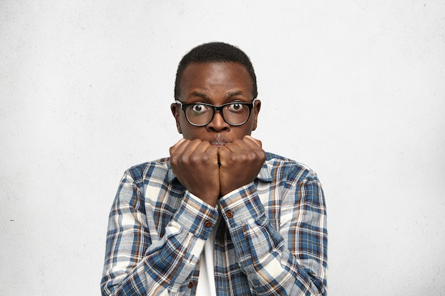 Afro-americano assistindo jogos sentindo-se nervoso, em pânico e em choque