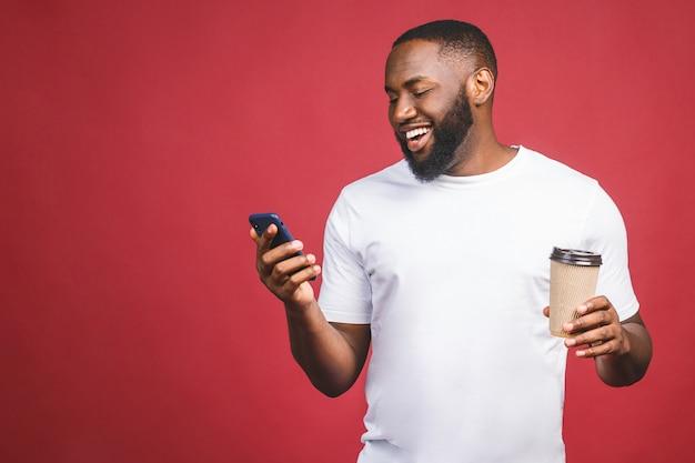 Afro-americano bonito com telefone móvel e tirar a xícara de café. isolado sobre o fundo vermelho.