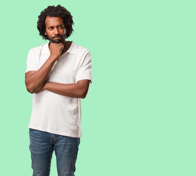 Afro-americano bonito duvidoso e confuso, pensando em uma idéia ou preocupado com algo