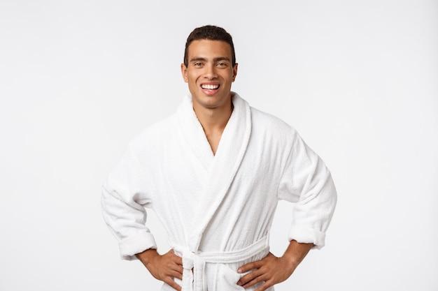 Afro-americano cara vestindo um roupão de banho com emoção feliz. isolado.