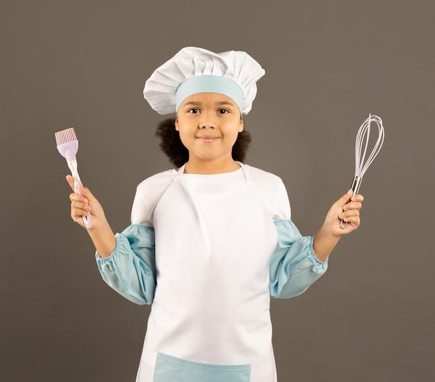 Afro-americano chef segurando utensílios de cozinha