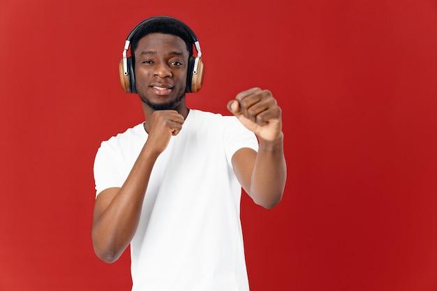 Afro-americano com camiseta branca usando fones de ouvido, amante da música, fundo vermelho