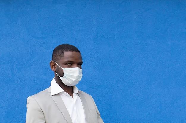 Afro-americano com uma máscara protetora sobre um fundo azul