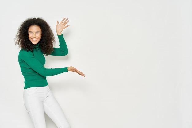 Afro-americano da mulher que mostra um produto no copyspace