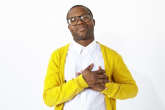 Afro-americano de aparência amigável e grato, mantendo as mãos no peito, demonstrando simpatia, reconhecimento e gratidão, estando de bom humor ou lisonjeado. emoções humanas positivas e linguagem corporal