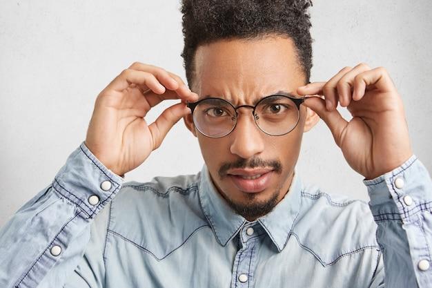 Afro-americano de pele escura parece rigoroso através dos óculos e usa camisa jeans