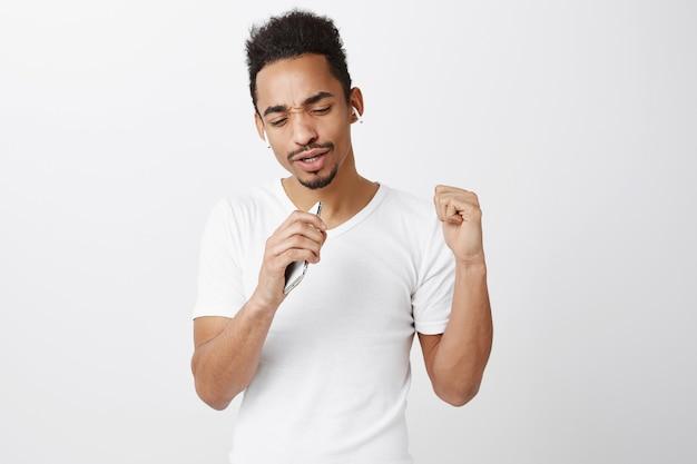 Afro-americano despreocupado tocando karaokê, cantando no microfone do smartphone e usando fones de ouvido sem fio