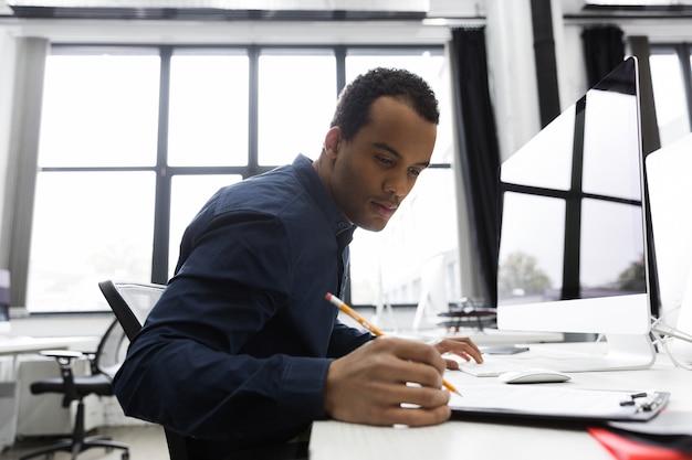 Afro-americano empresário fazendo anotações enquanto está sentado em sua mesa